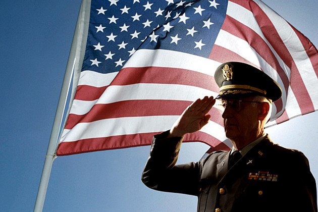 Silhouette of veteran US Army Colonel Chaplain wearing hat and saluting with an American flag flying behind him.