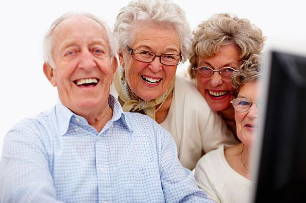 Happy senior man and women looking at computer