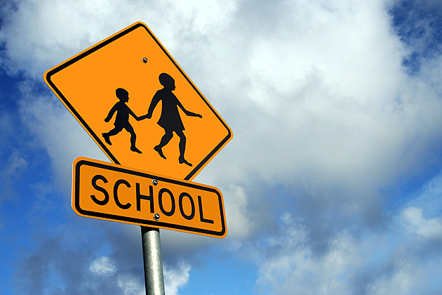 A yellow sign warning of a school zone